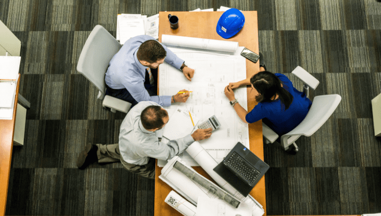 Accountant sit with colleagues, business owner, customer, client, on large paper work plan document on wooden table with books and plans to discuss budgeting and forecasting with Futrli #Forecasting #budgeting