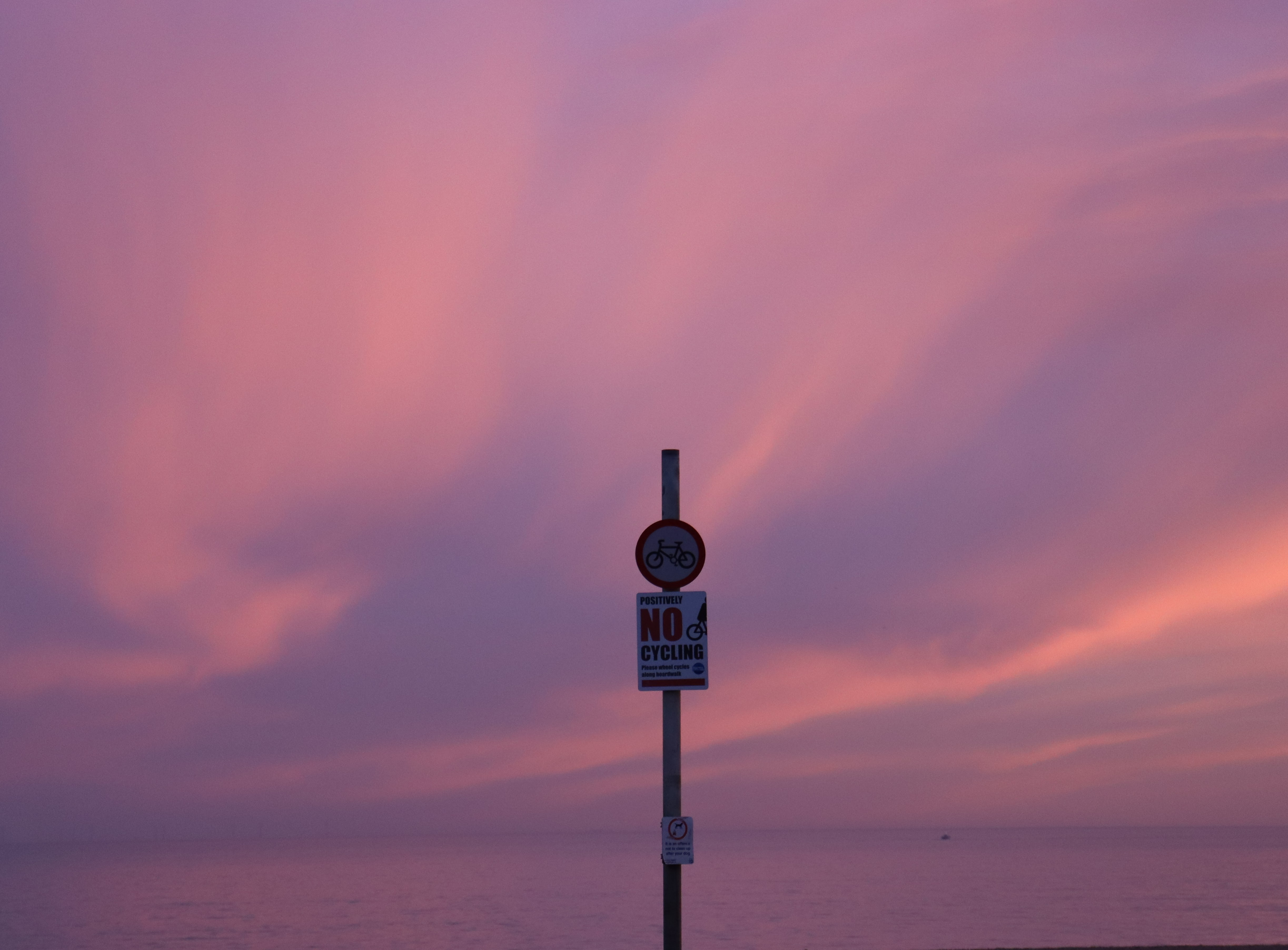 A violet sky with wavy clouds behind a no cycling sign.