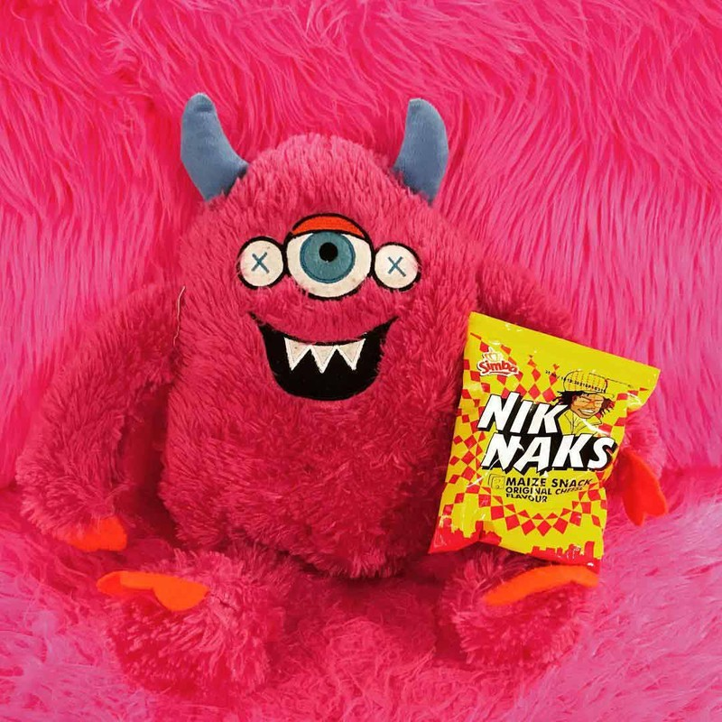 A pink stuffed toy with one eye and horns smiling and holding a bag of snacks