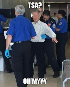 elderly asian man getting screened at airport by TSA