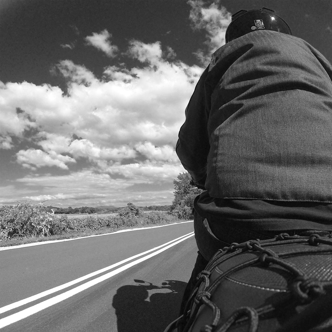 Black and white, me on a motorcycle taken from the back with the road and a cloudy sky in the background
