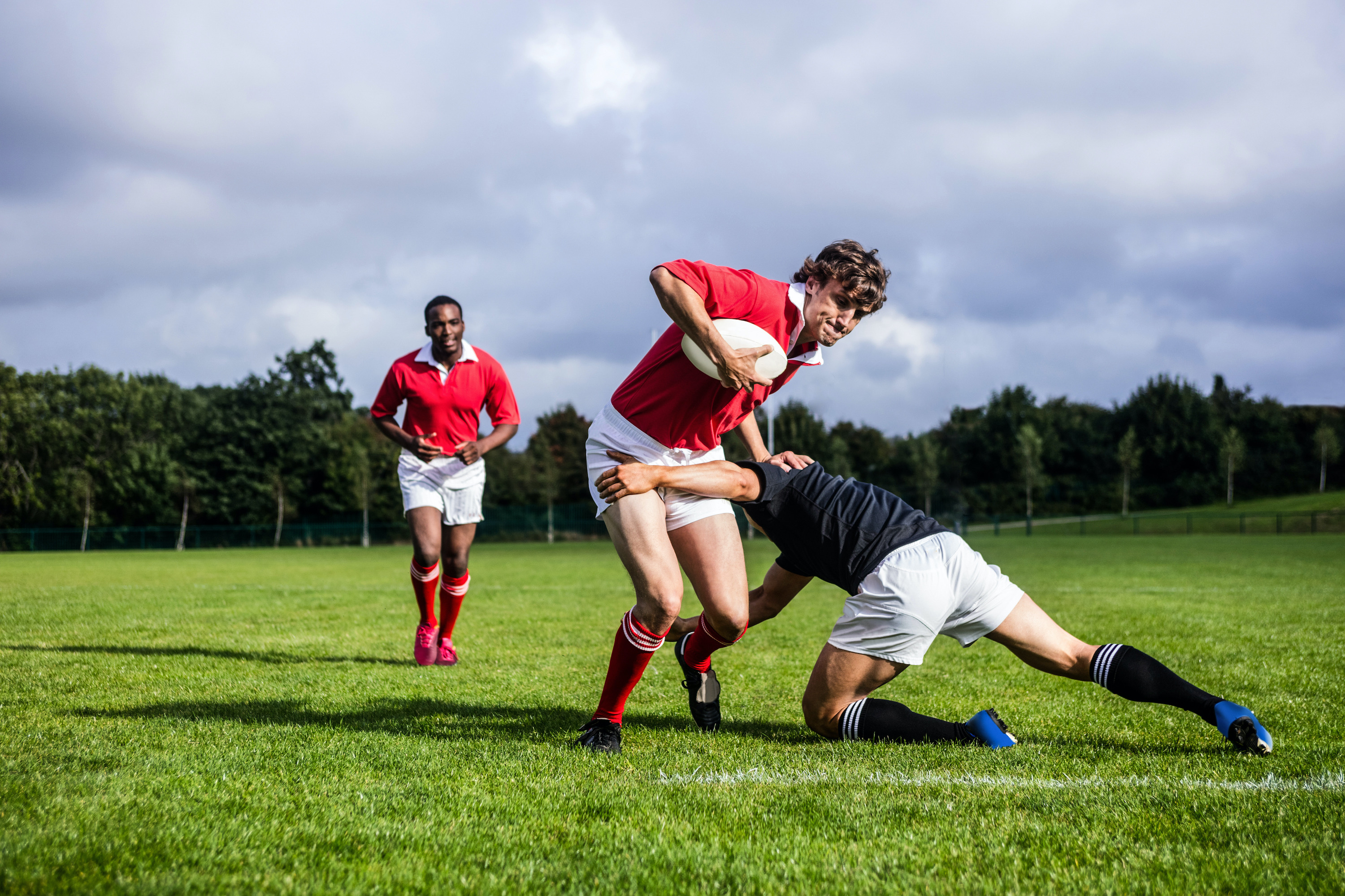Rugby players on a field. The player at the front has the ball and is being tackled by a player from the opposing team.
