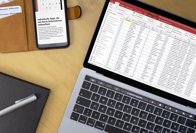 Laptop auf Schreibtisch mit Power BI auf Bildschirm, Stift und Smartphone