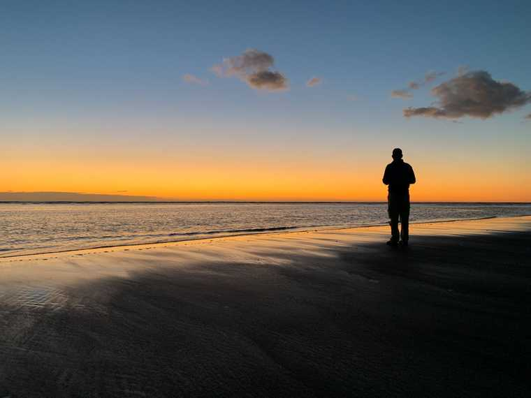 A silhouette of Jeb on the shore of Foxton Beach after sunset, the horizon glowing pinkish-orange.