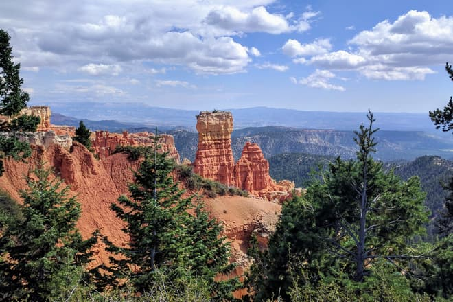 A fin of soft red and white rock extends from the South Wall of Bryce Canyon. It abruptly ends in two wide pillars of rock.