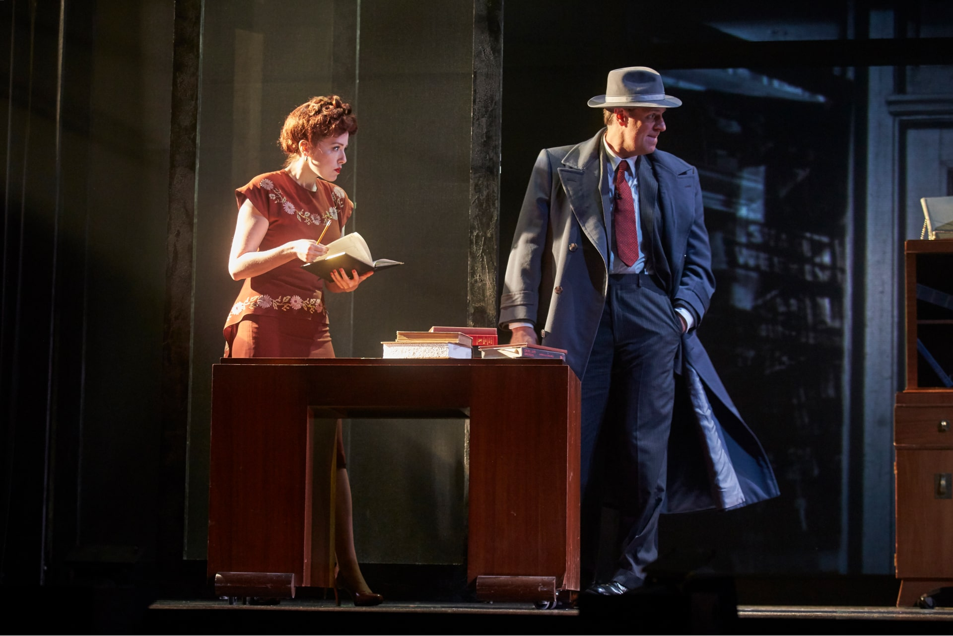 Man in suit and fedora perches on desk talking to woman in brown skirt-suit seated on chair – backlit by strong shaft of light.