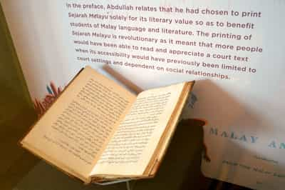 An opened book sits within a tall showcase. It contains Jawi script. In the showcase background, there is a printed graphic with a write-up about the Sejarah Melayu on it.