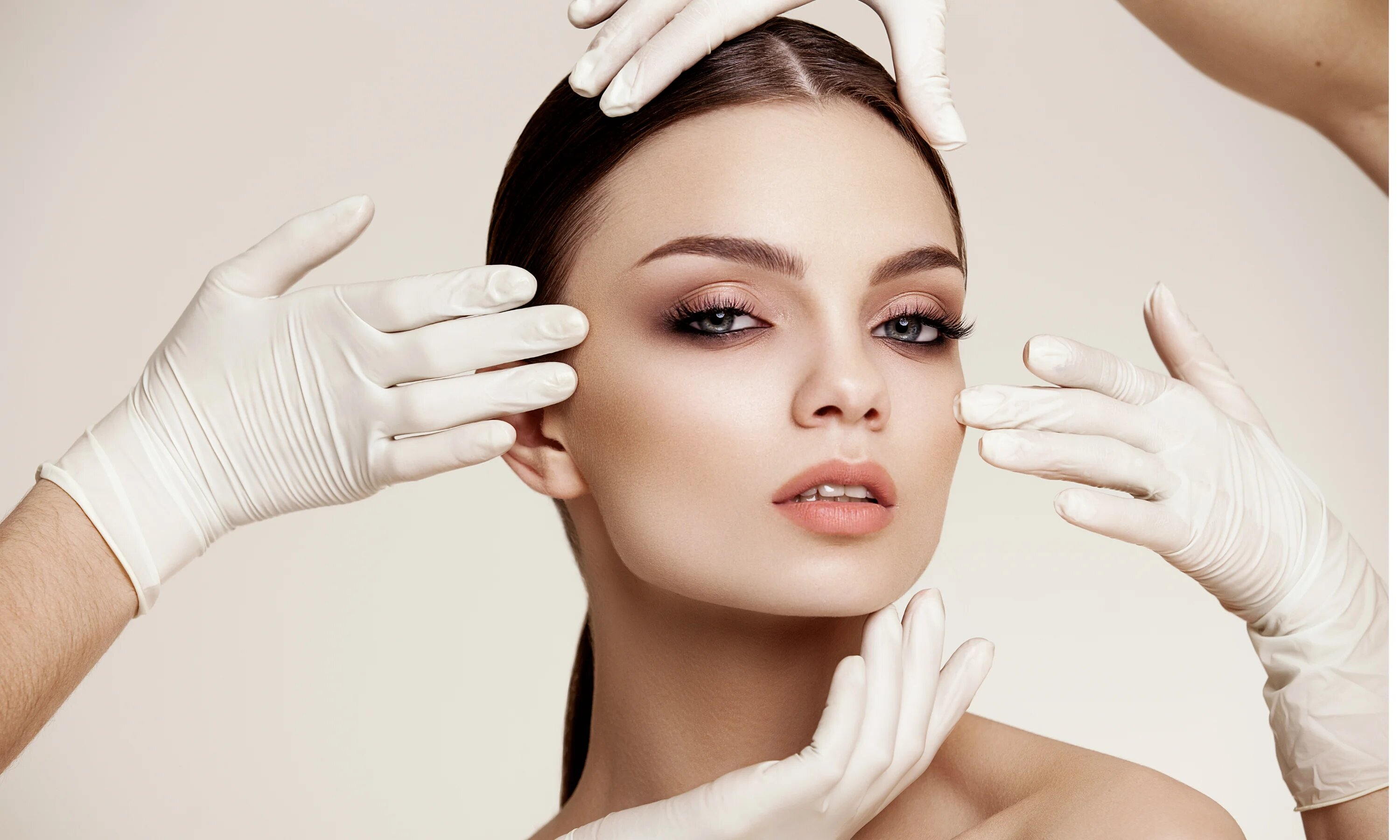 Female model surrounded by multiple hands wearing surgical gloves