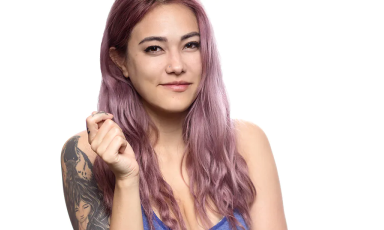 AvaGG smirking with purple hair and shoulder tattoo over white background with hand raised