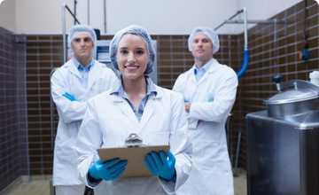 Qualité de Vie au Travail - 3 employés dont une femme, tous en blouse blanche avec des gants bleus et charlotte sur la tête avec en premier plan la femme tenant un document souriante. La photo dégage un sentiment de bien être. e une attitude