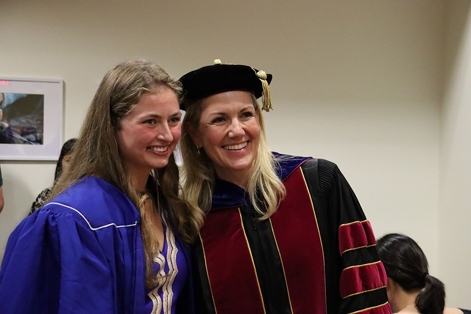 A professor and a student smiling