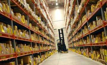 Supply chain - Une rangée d'un entrepôt contenant des racks bien remplis de produits en carton et un chariot élévateur à fourches est présent au fond de l'allée.