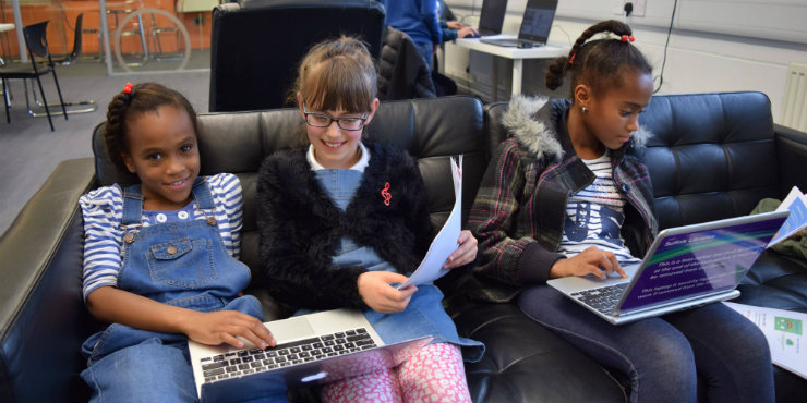 Three girls coding on laptops
