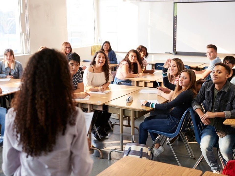 A diverse group of high school students sit at desks in a classroom.