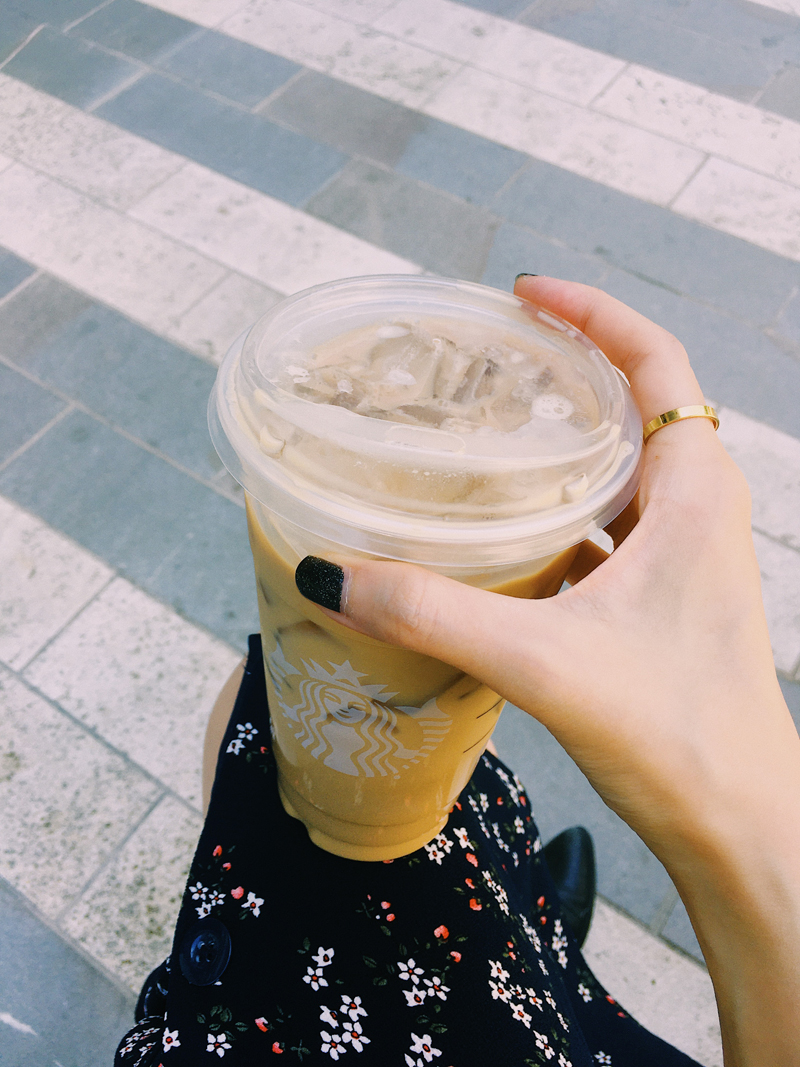 Holding a coffee drink.