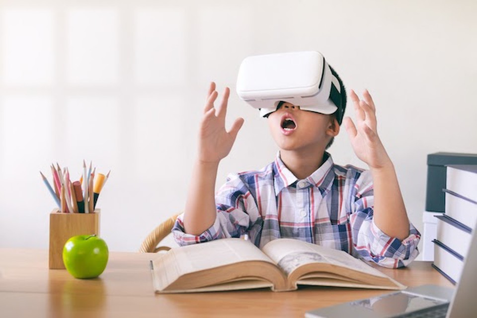 A young male student uses a VR headset at school, enjoying the benefits of virtual reality in education.