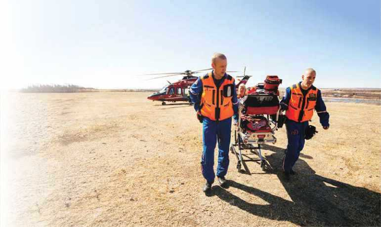 Stars paramedics pulling stretcher from helicopter on sand