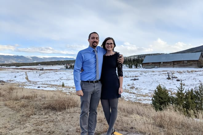 A man and woman pose outside together. Behind them is a snowy high country ranch, and in the distance the Rocky Mountains.