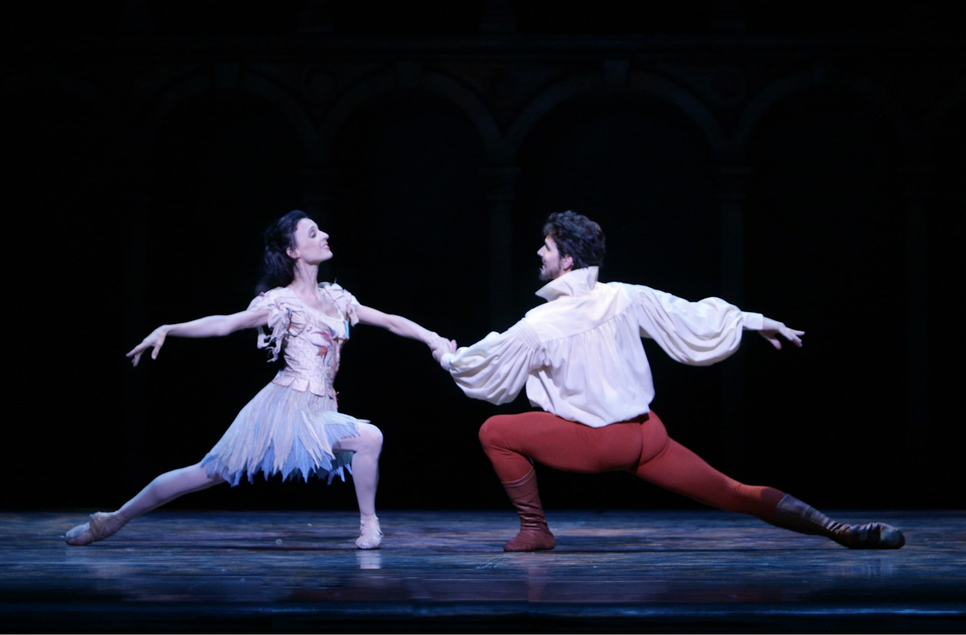 Ballerina in white feathery skirt holds hands with lunging dancer in orange tights.