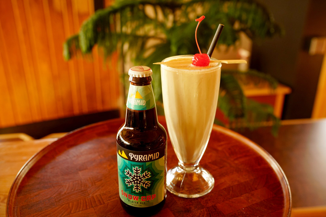 Bottle of Pyramid Snow Cap next to ice cream shake beer cocktail on a small table