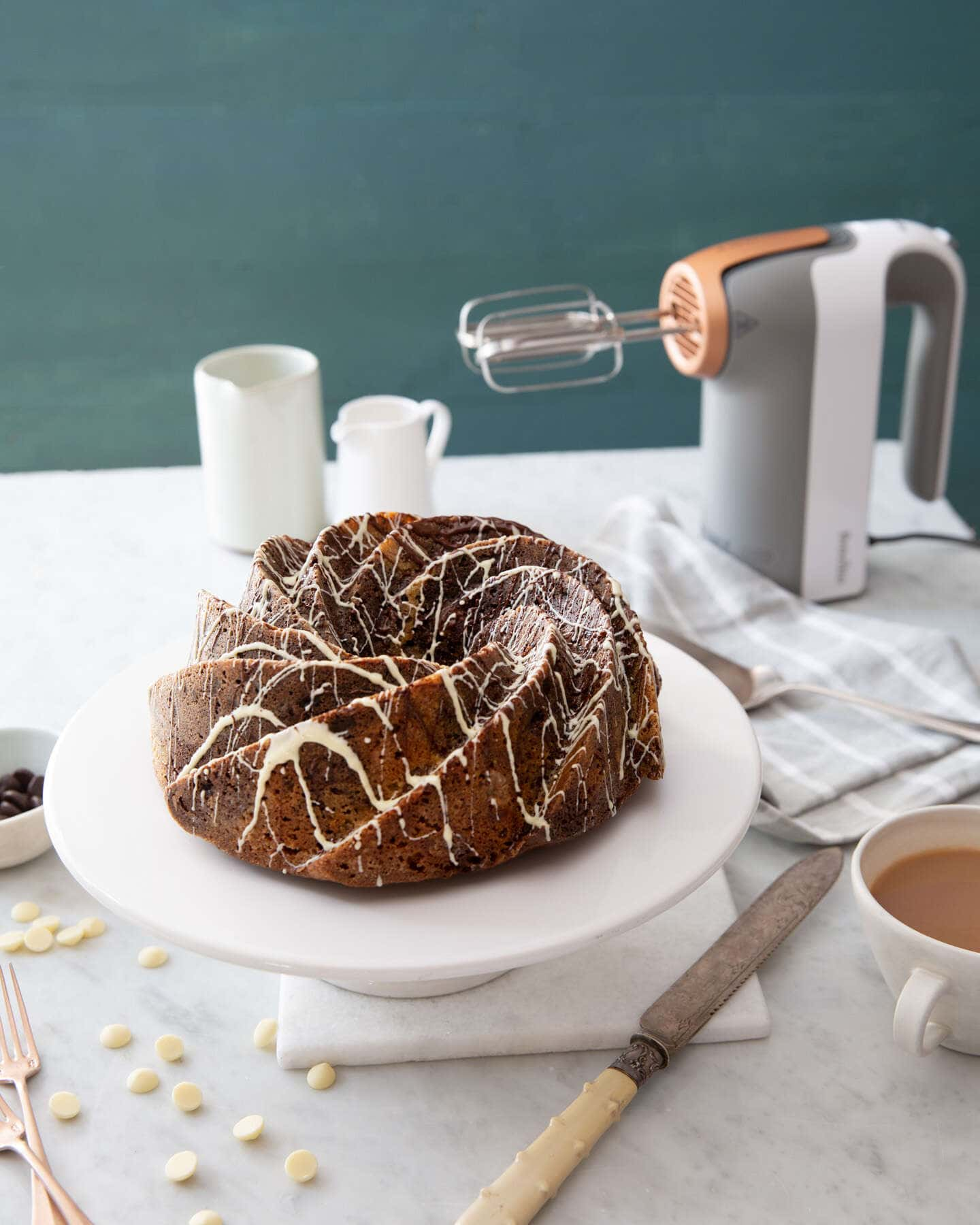 walnut swirl chocolate cake with a breville heat soft mixer in the background with a cup of tea and baking utensils.
