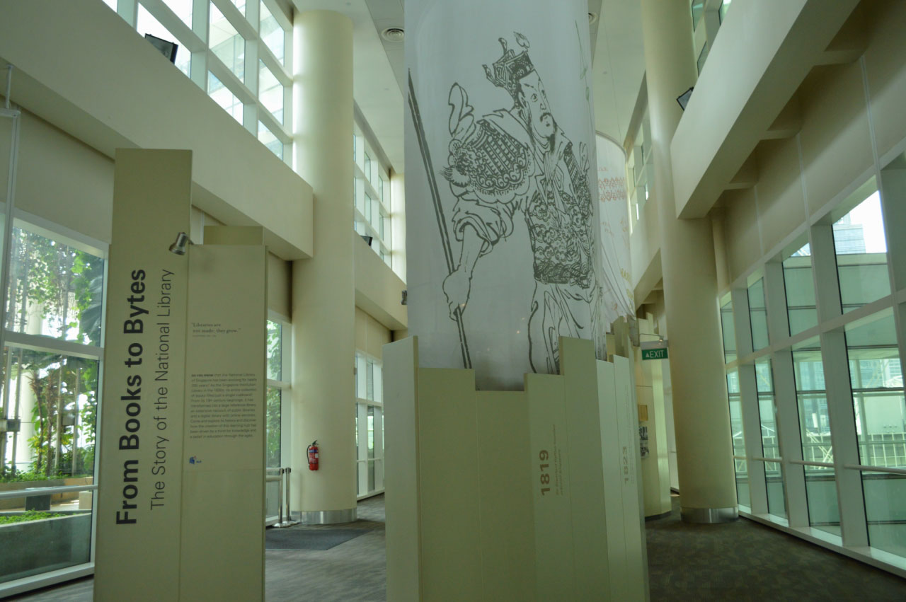 Photo of the front entrance of the From Books to Bytes gallery. The title and information wall is on the left. On the right is the main exhibition with a long cloth banner hanging from the tall ceiling. The banner has selected illustrations from books printed on it.