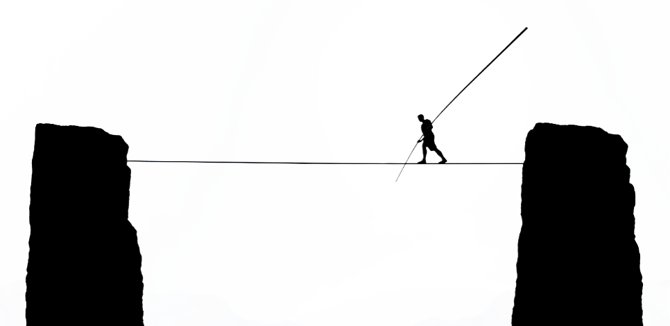 Man walking tightrope over canyon