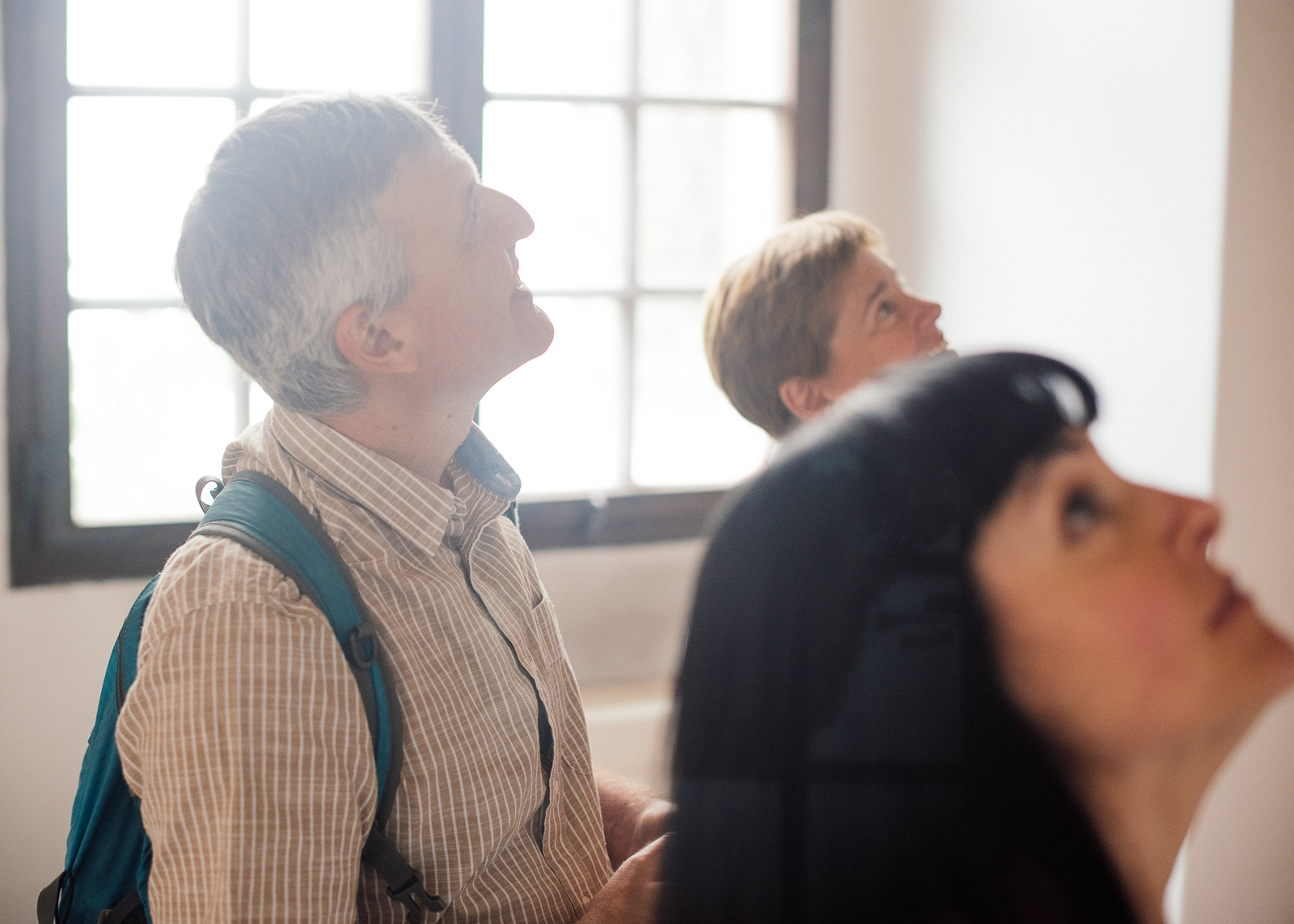 three people looking at up at the ceiling in the Theological Hall