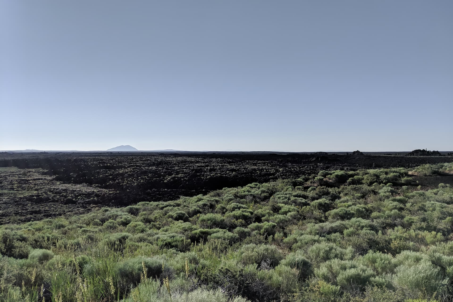 Desert scrubland abruptly ends in a dark, jagged lava field that stretches to the horizon. In the distance, an imposing lava dome rises above the horizon.