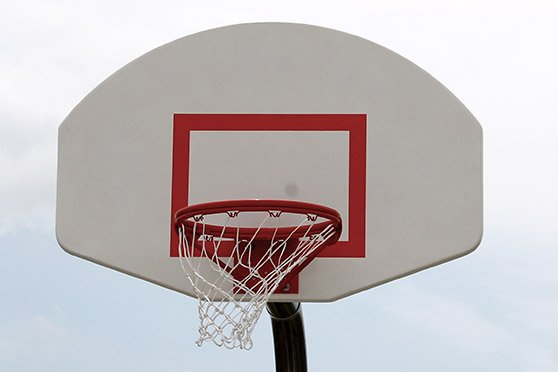 Outdoor basketball hoop with white backboard.