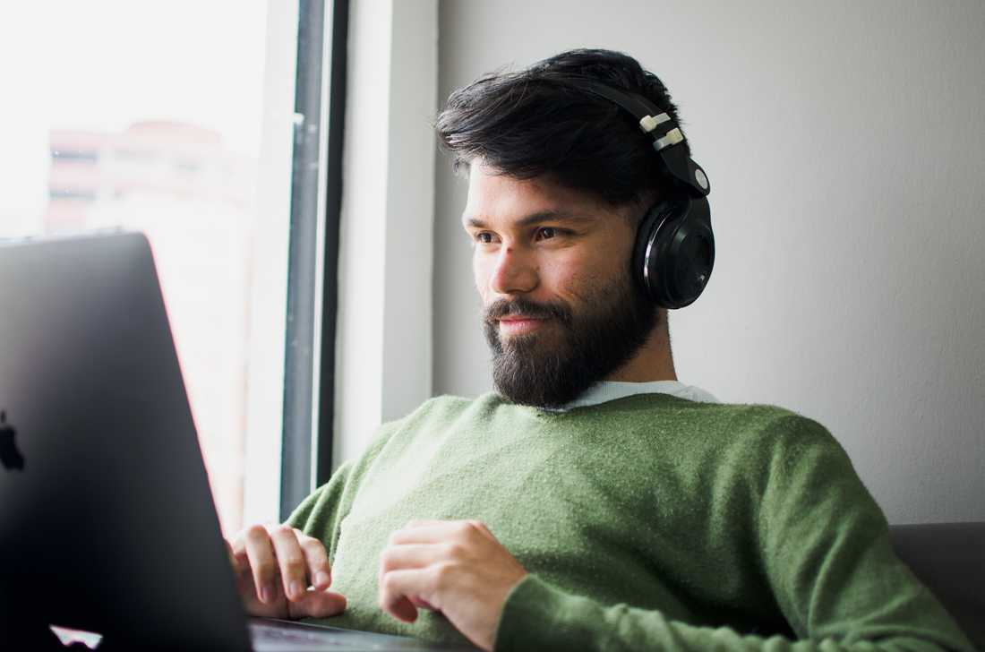 man wearing headphones while looking at MacBook