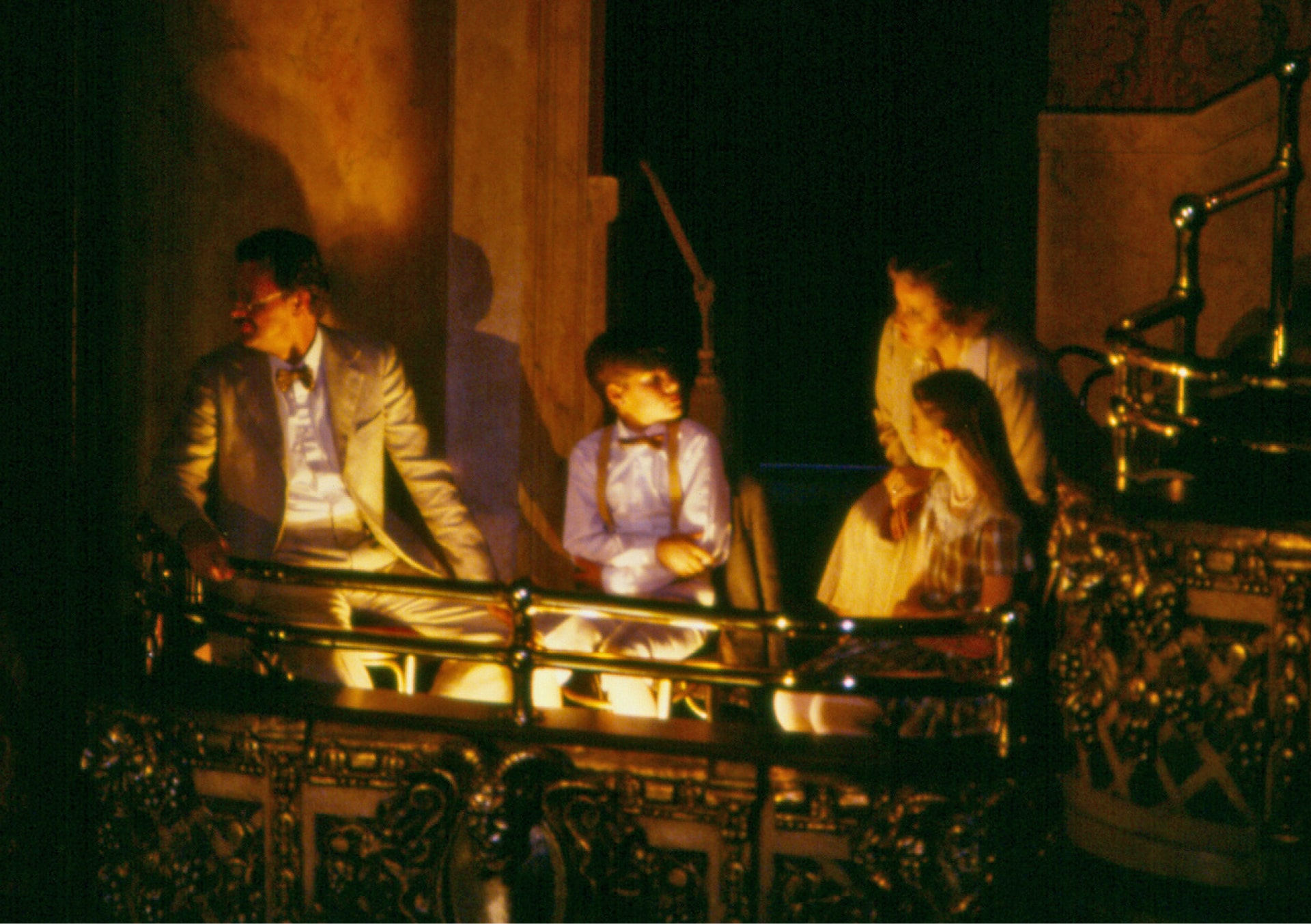 Family in theatre box with gold railings lit by lights at their feet look towards stage.