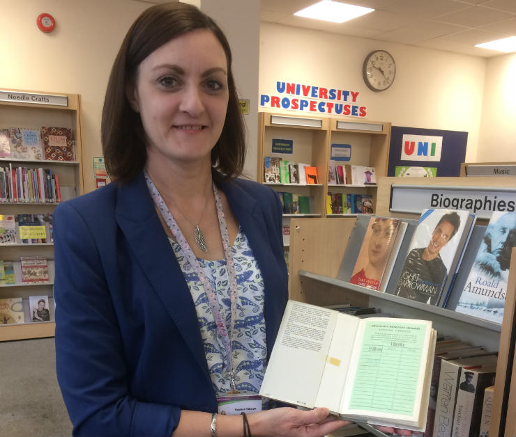 Lowestoft Library staff member Rachel Gibson with <cite>The Metaphysical Poets</cite> by Jim Hunter, which was recently returned 52 years late