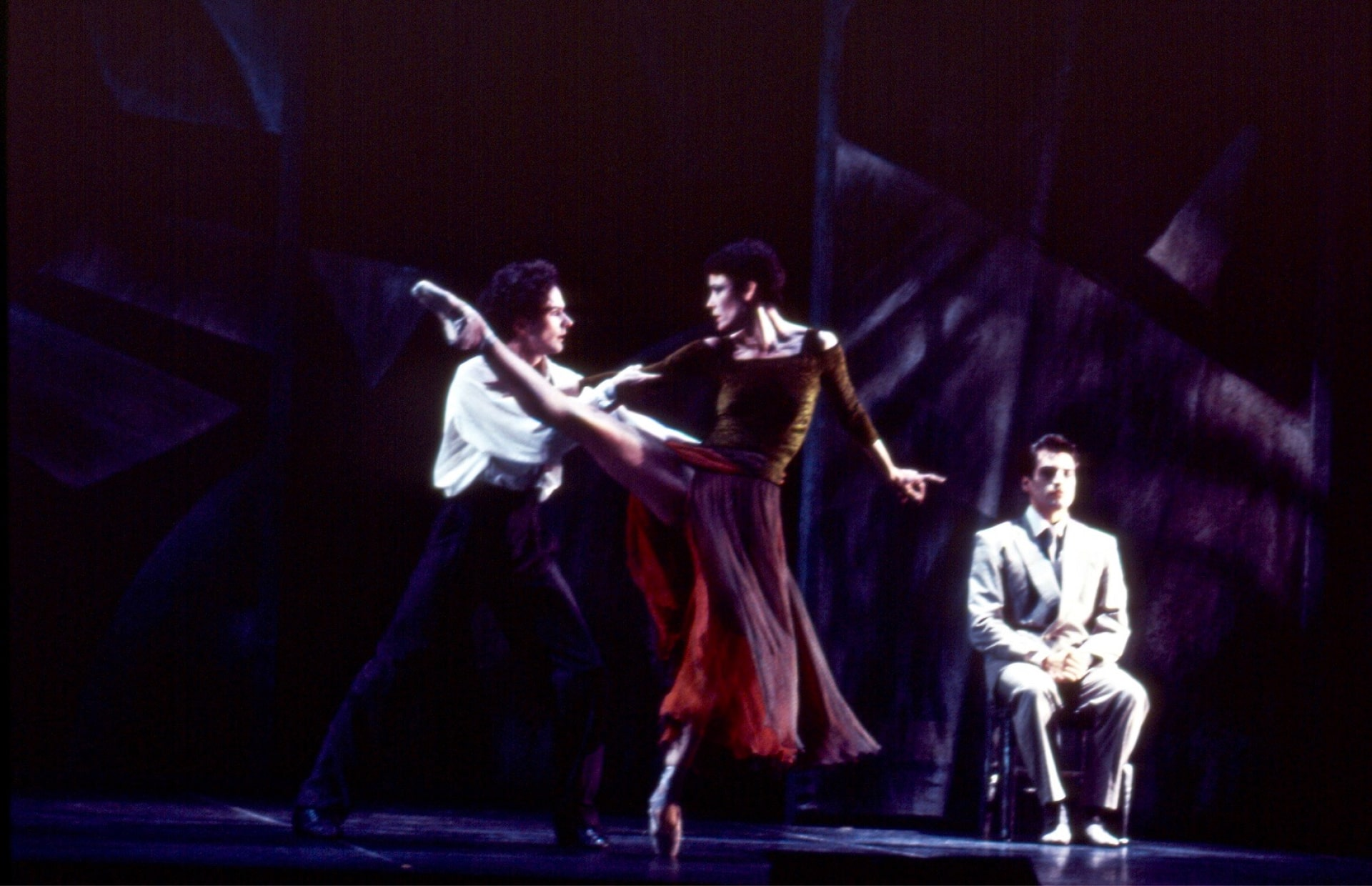 Dancer holds ballerina in red skirt with leg extended, watched by seated man in white suit against dark geometric background.