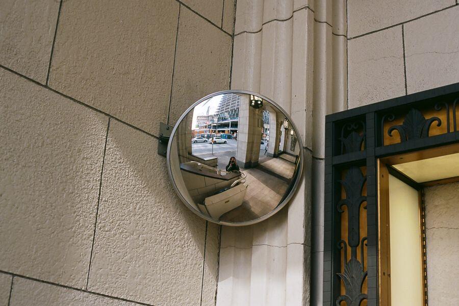 Mirror selfie in a circular convex mirror on the street
