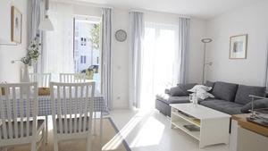 Wohnzimmer mit Sofa, Esstisch und Terassenzugang