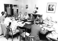 Old black and white photo of 12 men in suits seated around a conference table