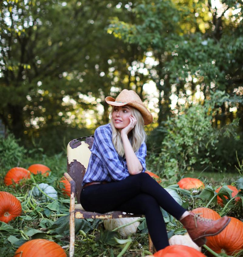 Sarah Frey sitting in a pumpkin field