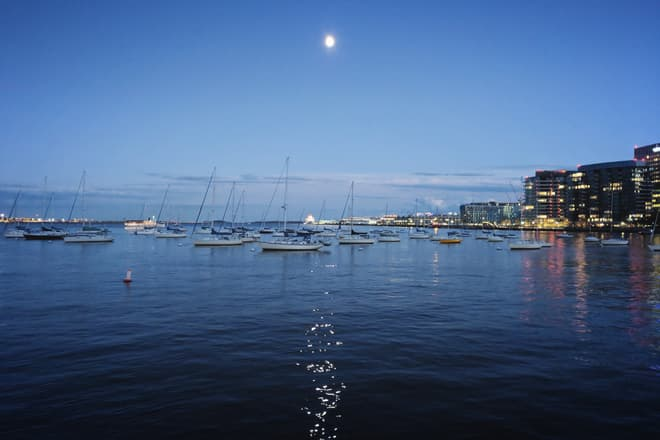 The Moon over Boston Harbor at dusk.