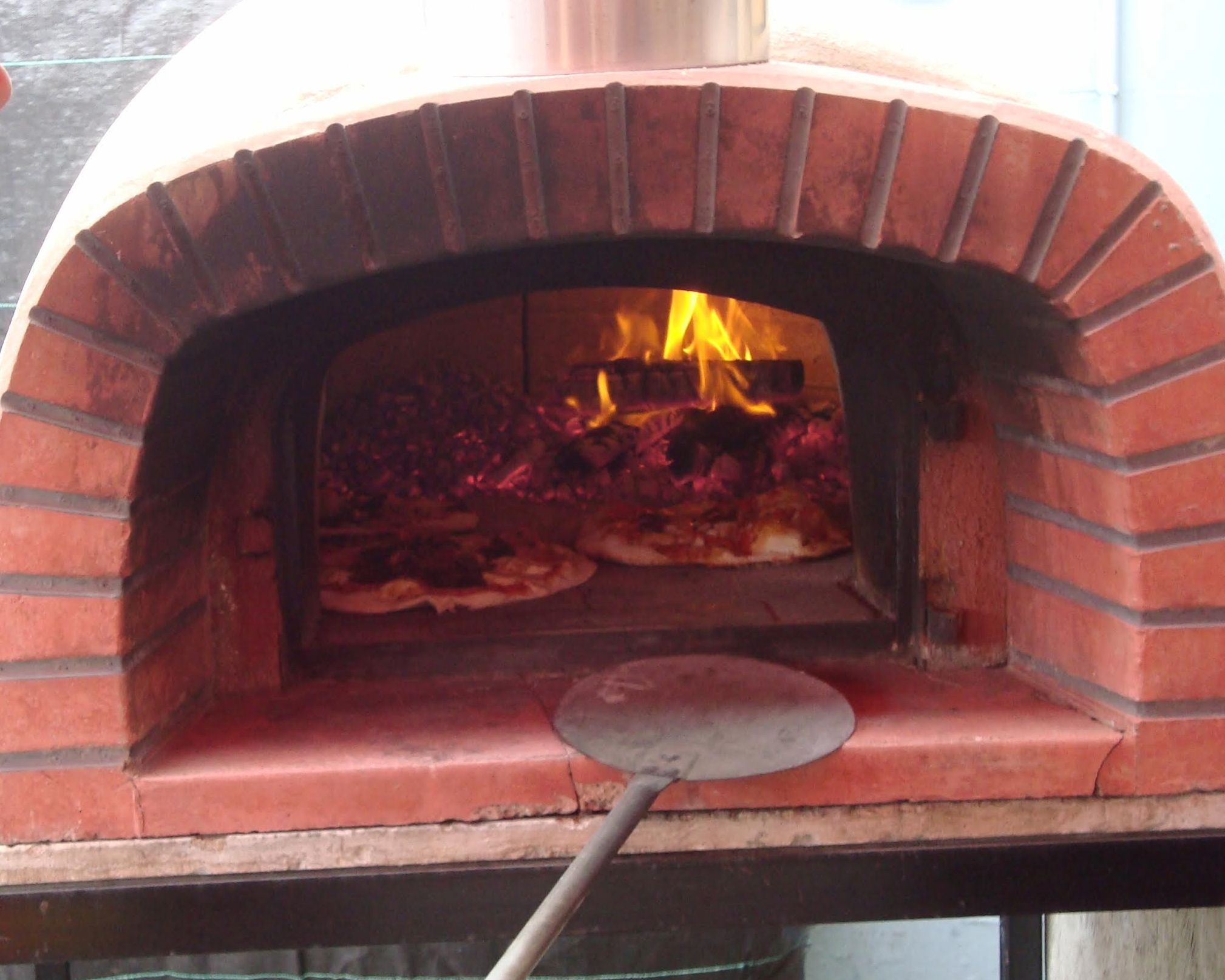 Al Forno wood oven cooking pizza in Auckland.