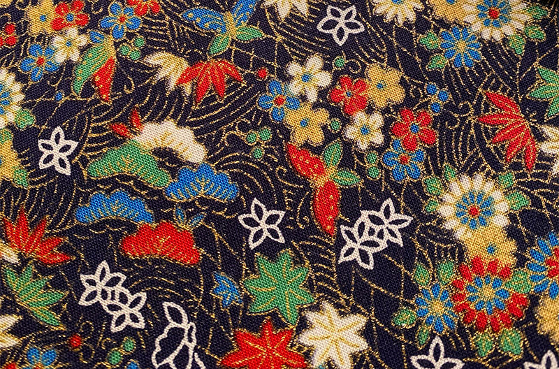 Gilded, floral Japanese fabric. Between the various blossoms float some butterflies.