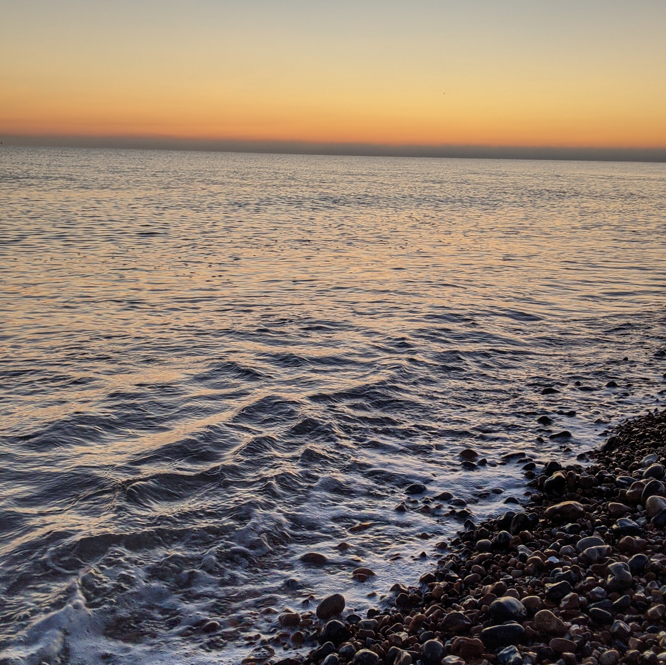 Calm sea with small wave breaking onto shingle and an orange sky.