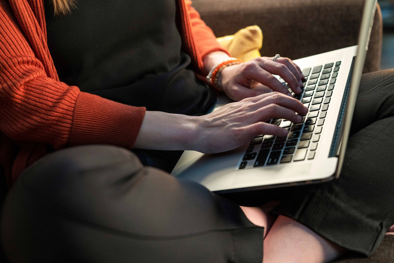 Sitting woman in red sweater typing on her laptop