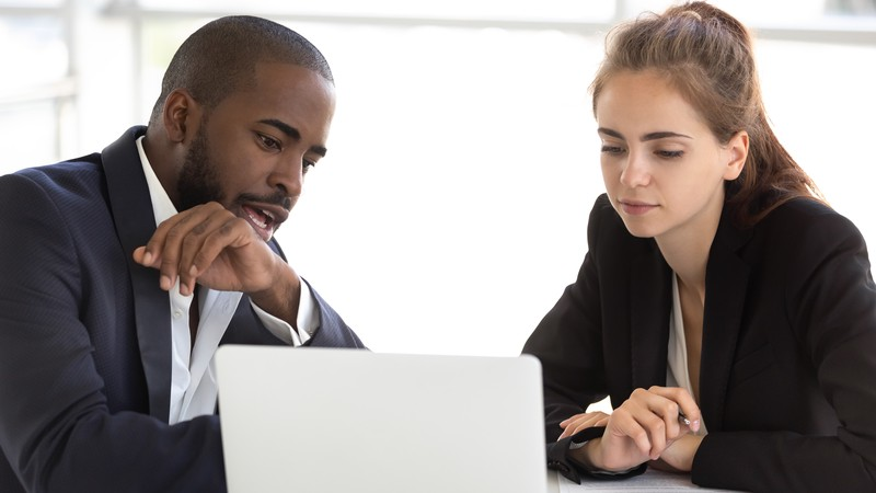 A career coach and client seated at a table reviewing a laptop screen.