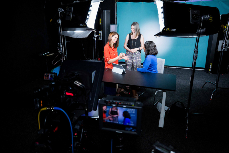 Three colleagues talking in a video production studio