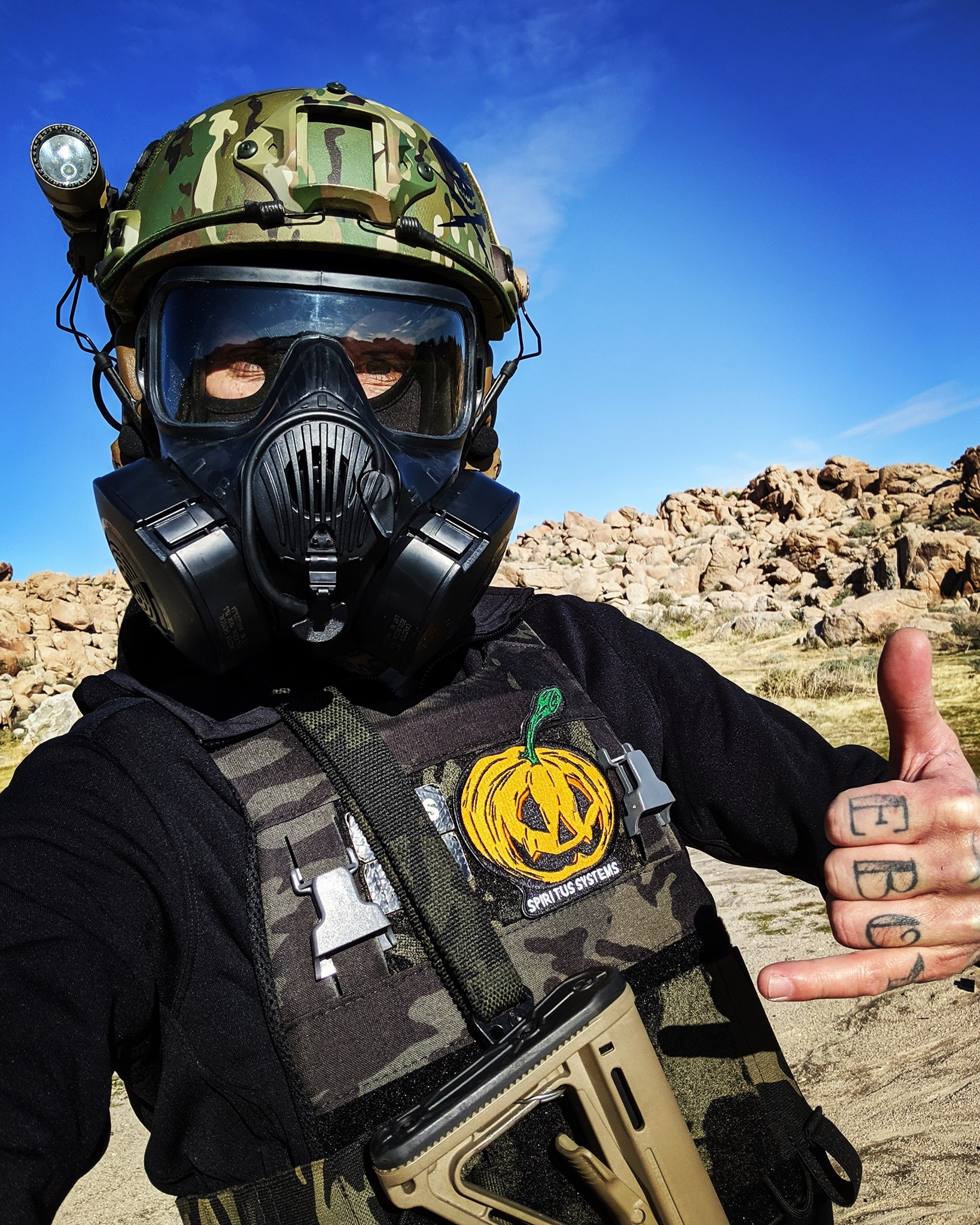 Zamudio poses in a gas mask and body armor giving a 'surf's up' hand gesture. There's tattoos on his fingers that spell out 'white boy.'