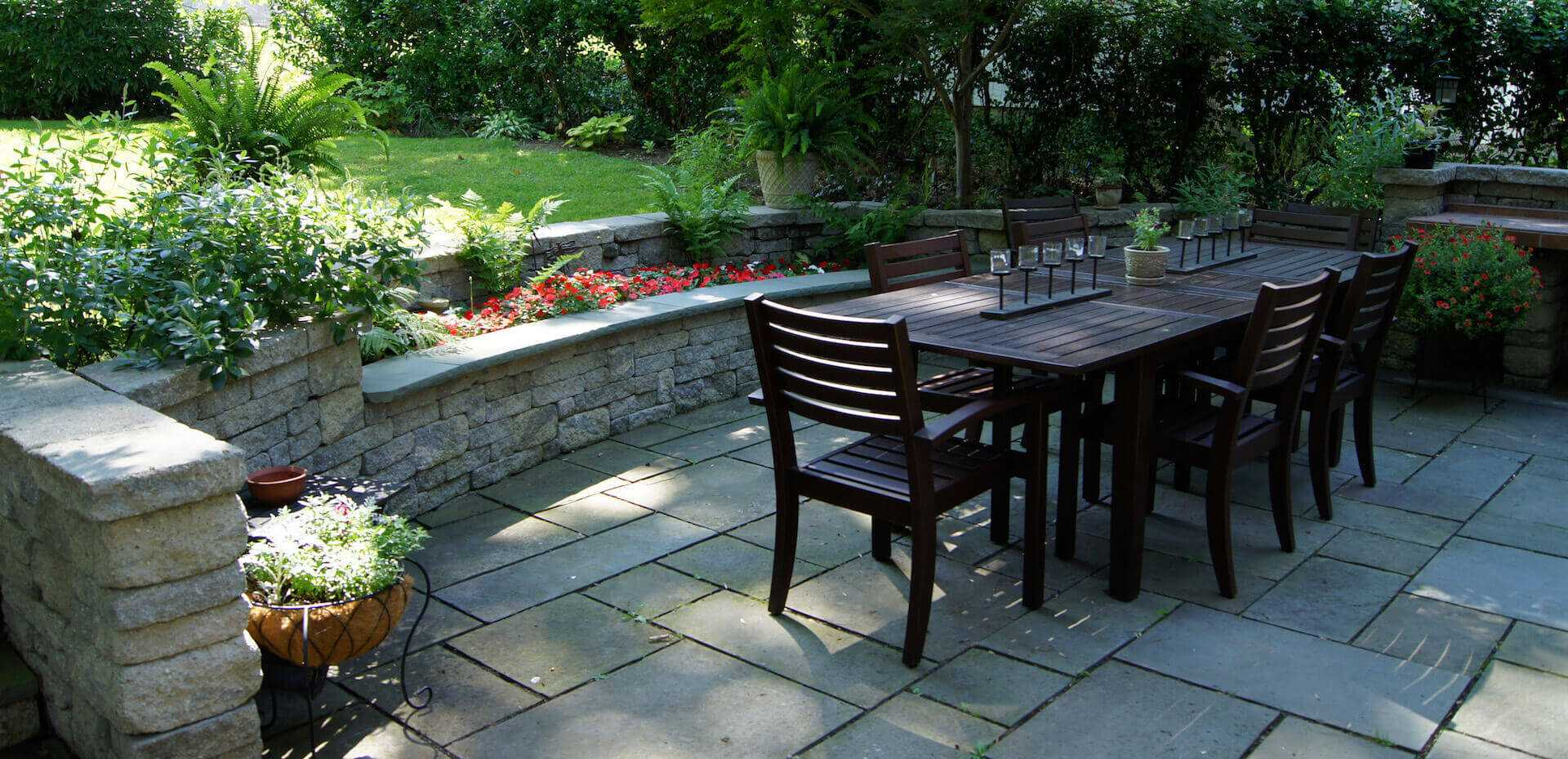 outdoor dark wood table surrounded by stone landscape architecture