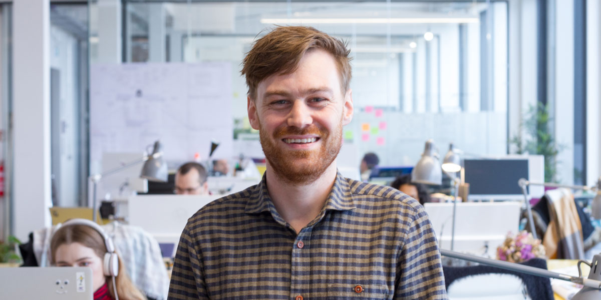 A web developer smiling at the camera against an office background