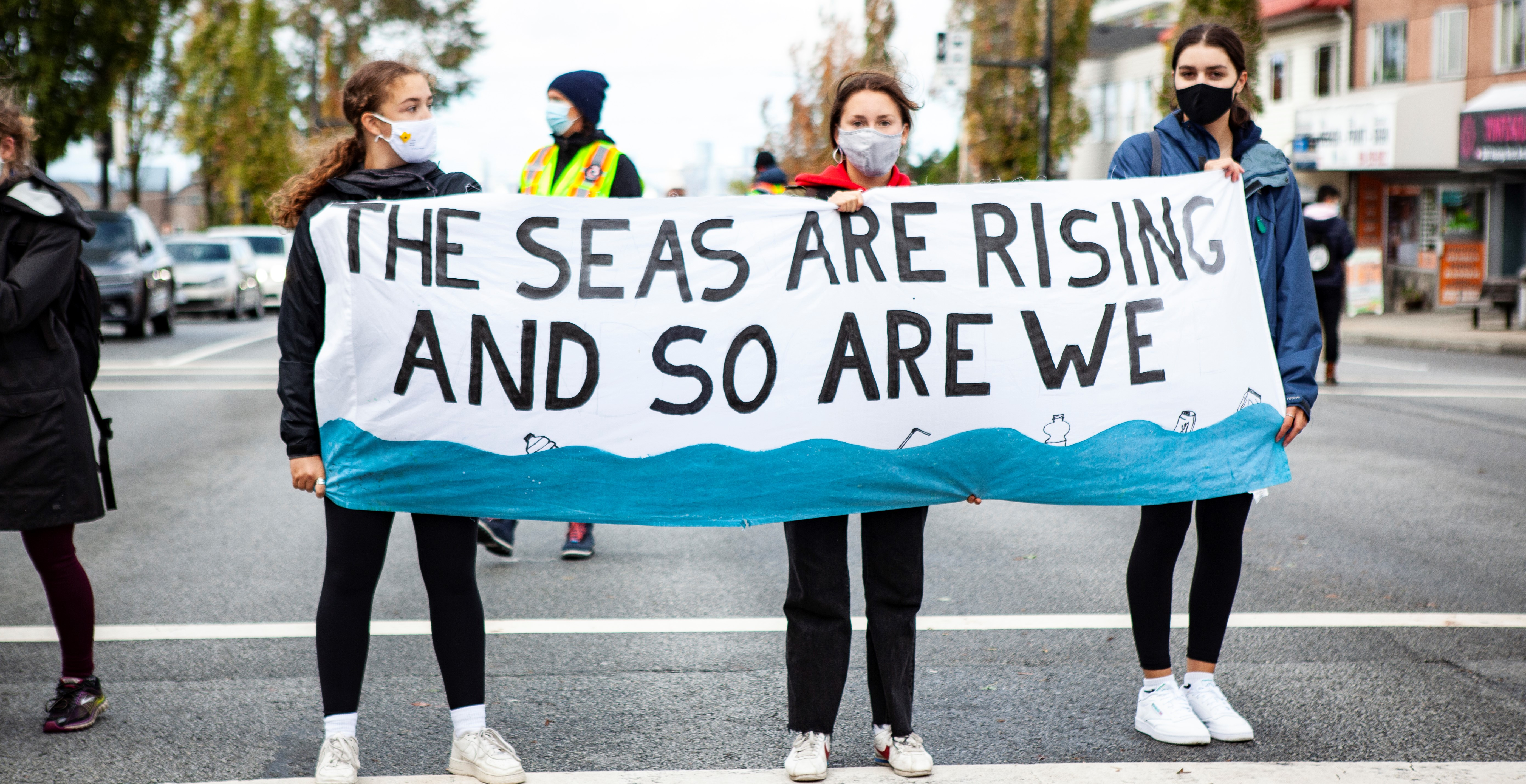 High school students holding a banner with text stating: The seas are rising and so are we