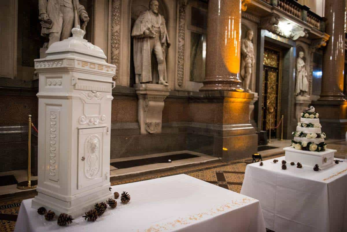 Wedding postbox and wedding cake inside a grand hall